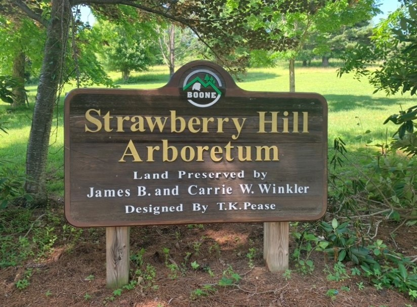 Wooden sign with Strawberry Hill Arboretum printed